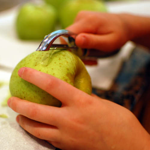 Little hands learning to use the vegetable peeler. She did one apple before turning the job over to Ted.